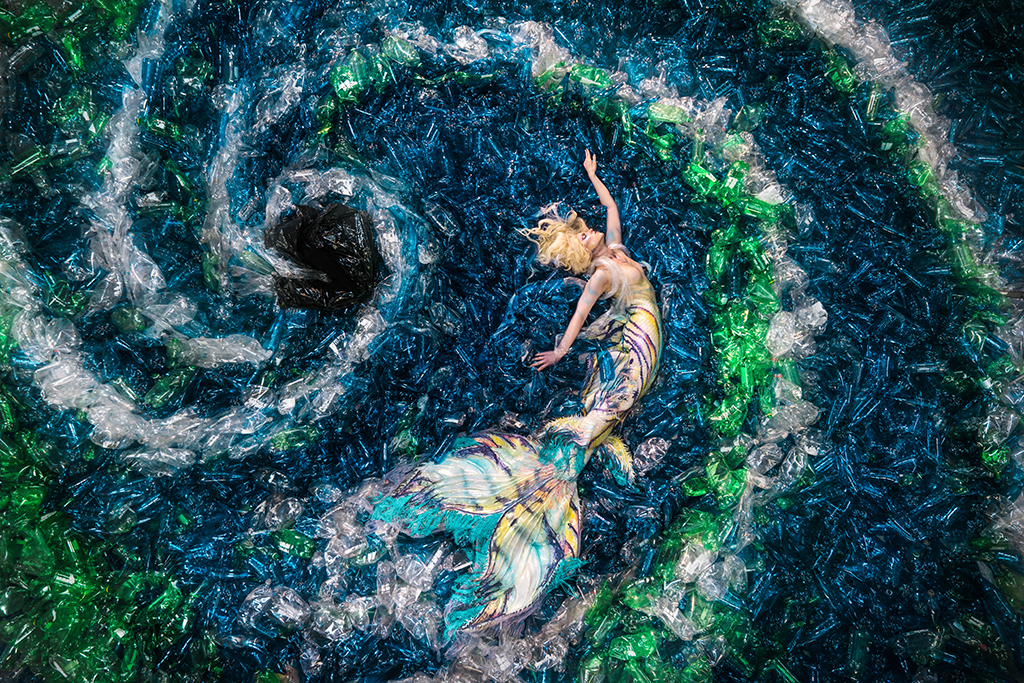 A mermaid photographed on 10,000 plastic bottles to raise awareness about plastic pollution.