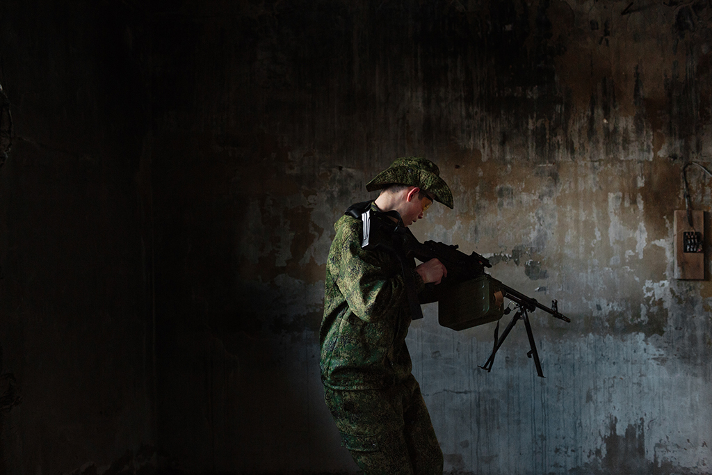 "Artyom Baklashkin (17), a student at the local secondary school in the village of Diveevo, stands guard in an abandoned building with a group known as the ""Survivalists,"" April 6, 2016, Russia. Survivalists train young adults to survive future wars and post-apocalyptic life and meet weekly for tactical drills. They use air-soft guns for the practice and competition. From ""Toy Soldiers."""