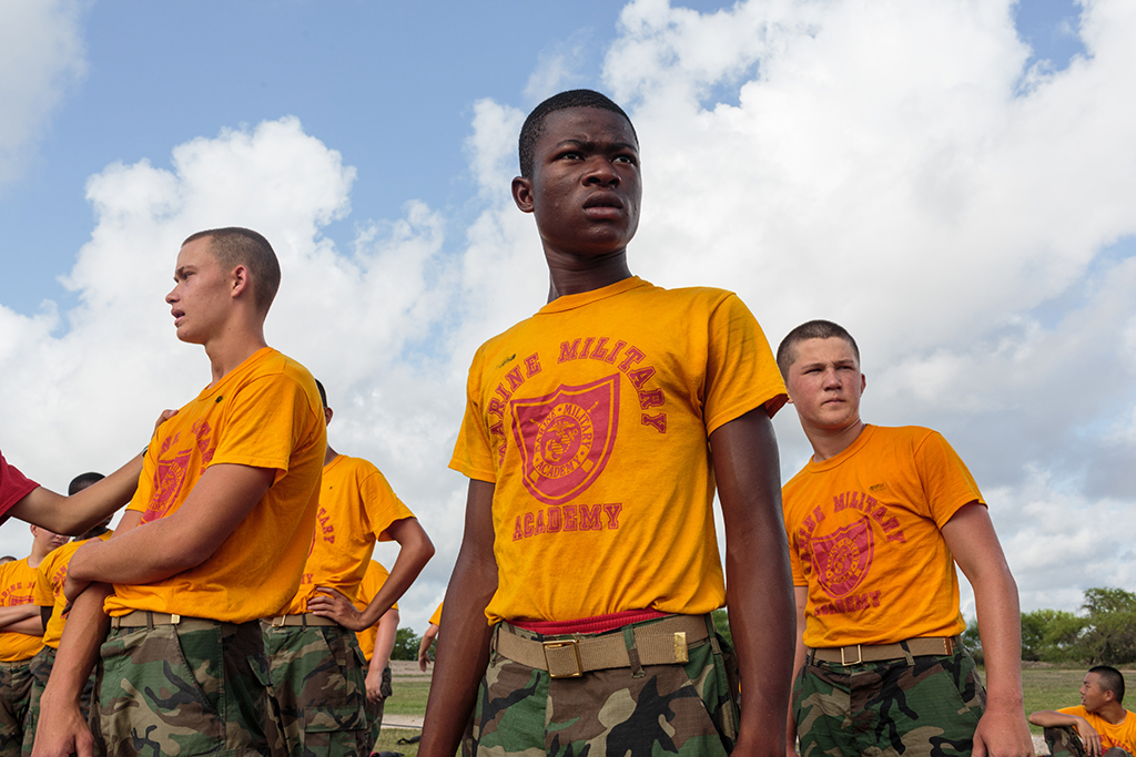 "Students prepare to begin an afternoon of physical drills at Marine Military Academy, an all-boys institution. MMA hosts a summer camp on its academic campus in Harlingen, Texas, July 17, 2017. The camp draws boys from around the world, ages 12-18, with around 300 cadets in attendance. From part one of ""Beckon Us From Home."""
