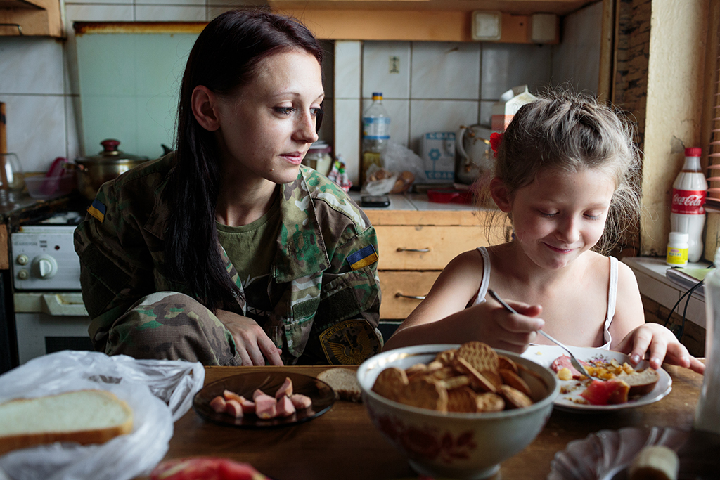 "Nastya (26) and her daughter Jenya (7) in their kitchen's apartment in Kiev, Ukraine, Sept. 10, 2016. Nastya, who regularly goes to the front line of combat, is a volunteer heading to the ATO (anti-terrorist operation) zone the following week. She is not affiliated with any government organization or under contract with the army. She has two children who she regularly leaves at home while heading to the front line to support soldiers. From ""The Right to Fight."""