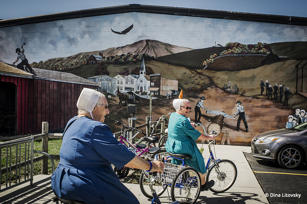 Two women pass by a mural