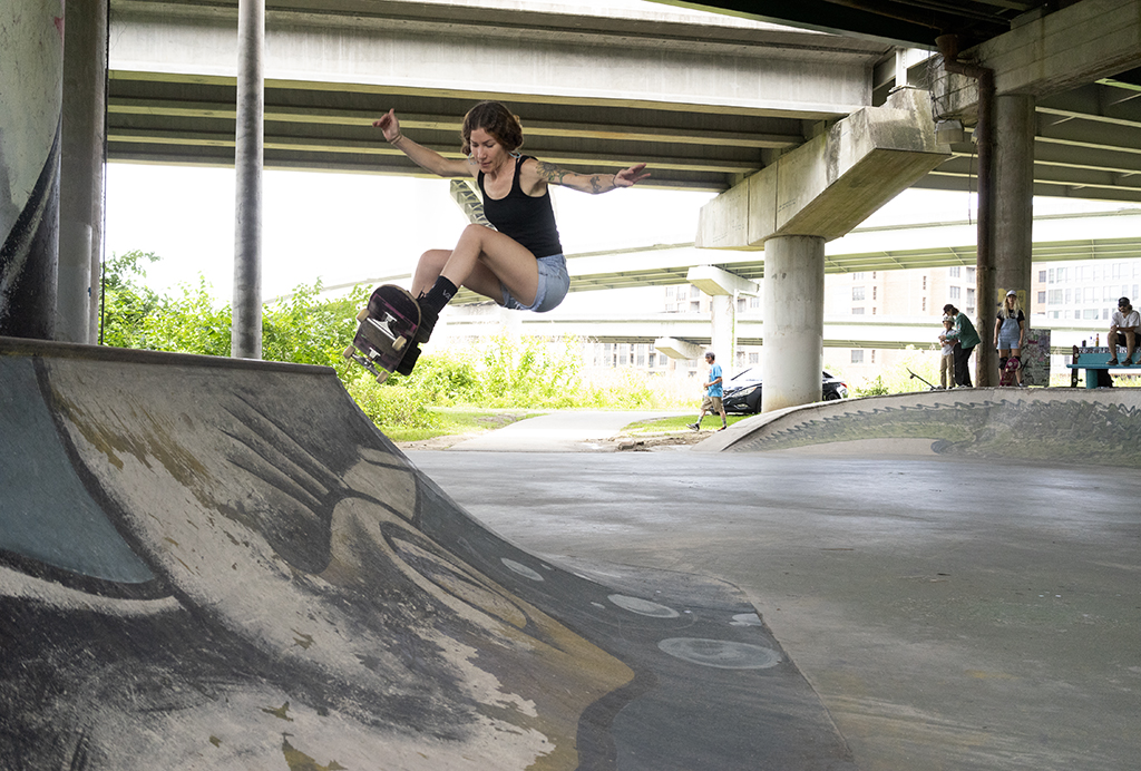 Ashley Wade catching air at a DIY skate spot